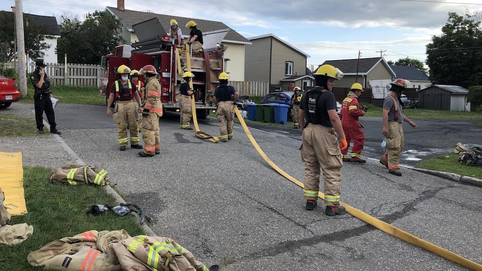 Pompiers manipulant un boyau d'arrosage.