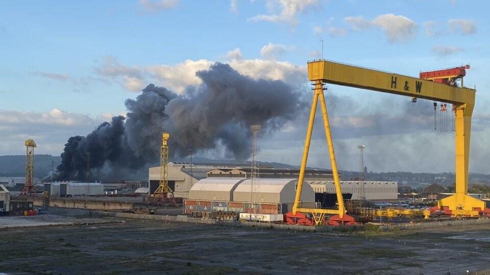 Une épaisse colonne de fumée s'envole dans le ciel au-dessus de l'usine dans le port.