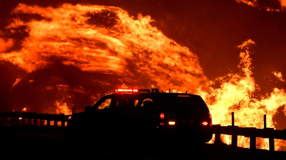 Le brasier semble poussé par les flammes, soufflées devant un camion d'urgence.