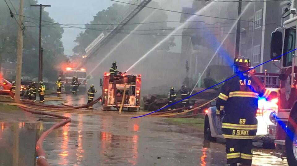 Des lances d'incendie arrosent l'immeuble. Un pompier est debout à l'avant-plan, les bottes dans l'eau.