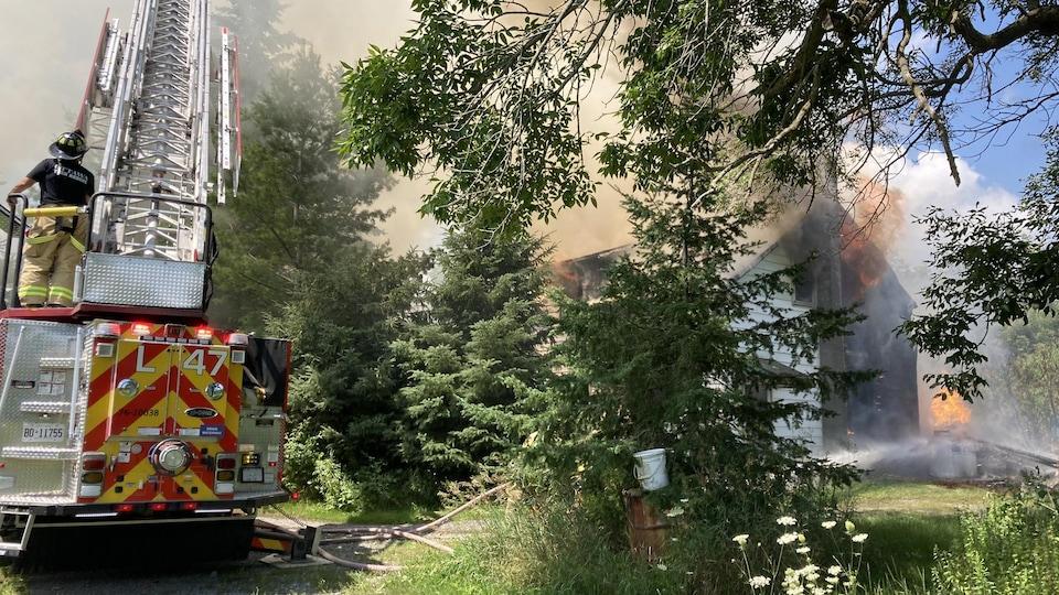 Des pompiers sur un camion tentent de maîtriser un feu dans une maison.