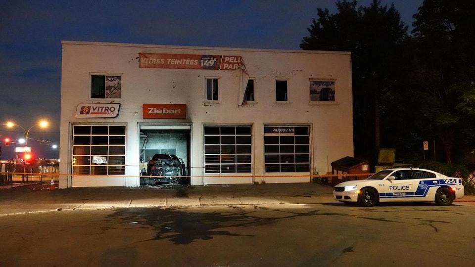 La façade de l'immeuble devant lequel se trouve une voiture de police.