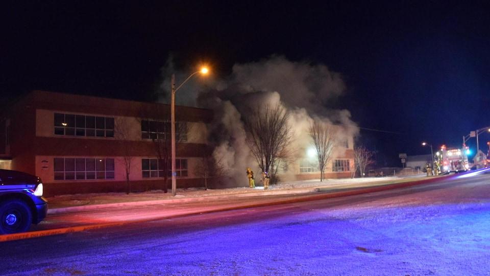 Des pompiers éteignent un feu dans une école primaire.