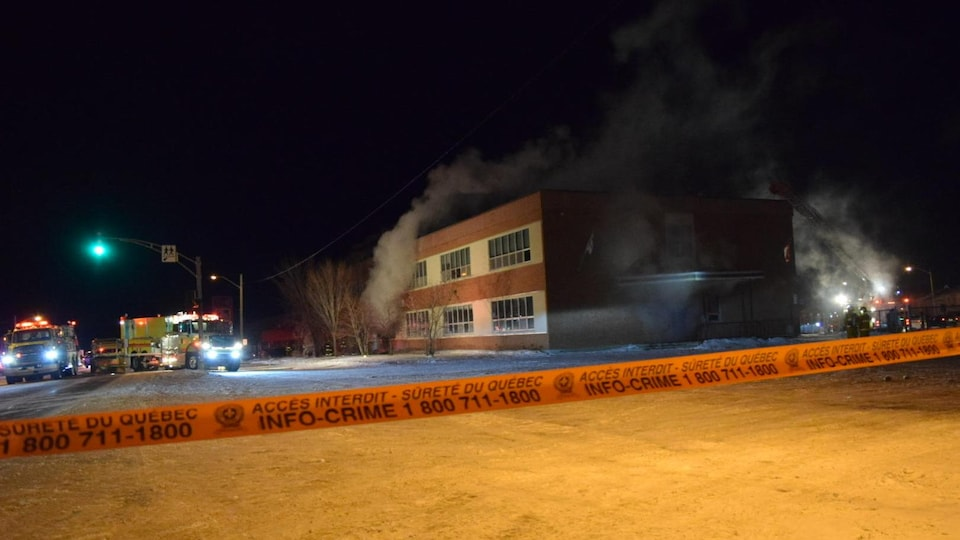Un ruban de sécurité devant une école dont s'échappe de la fumée.