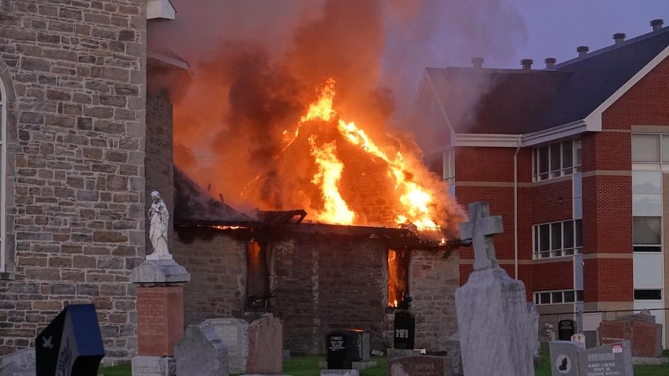 Les flammes ravagent le toit de la sacristie.
