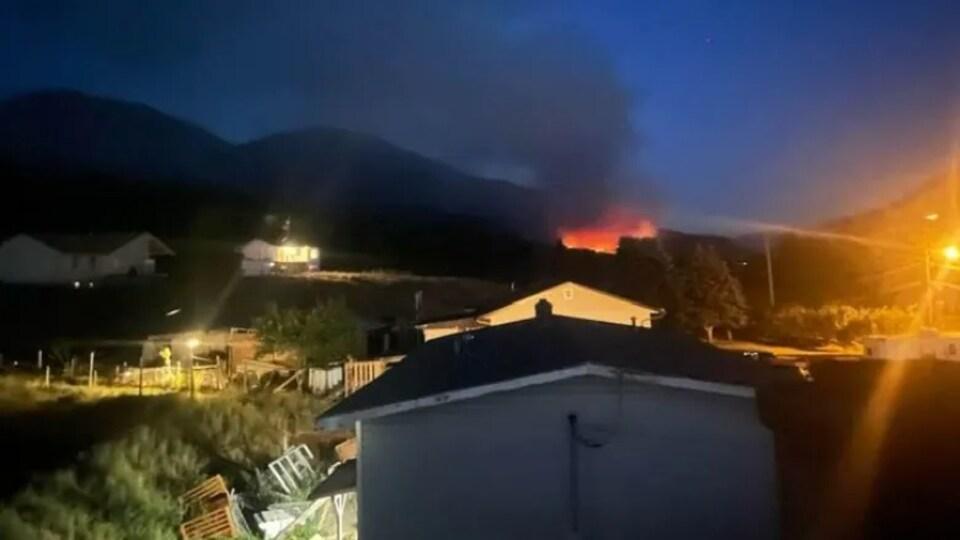 Quelques bâtiments à l'avant-plan avec un feu au loin.