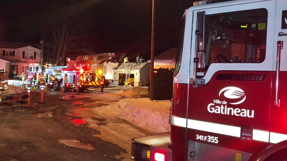 Un camion du service d'incendie de Gatineau dans un quartier résidentiel la nuit.
