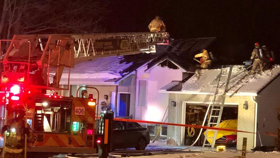 Des pompiers sont sur la toiture d'une résidence.