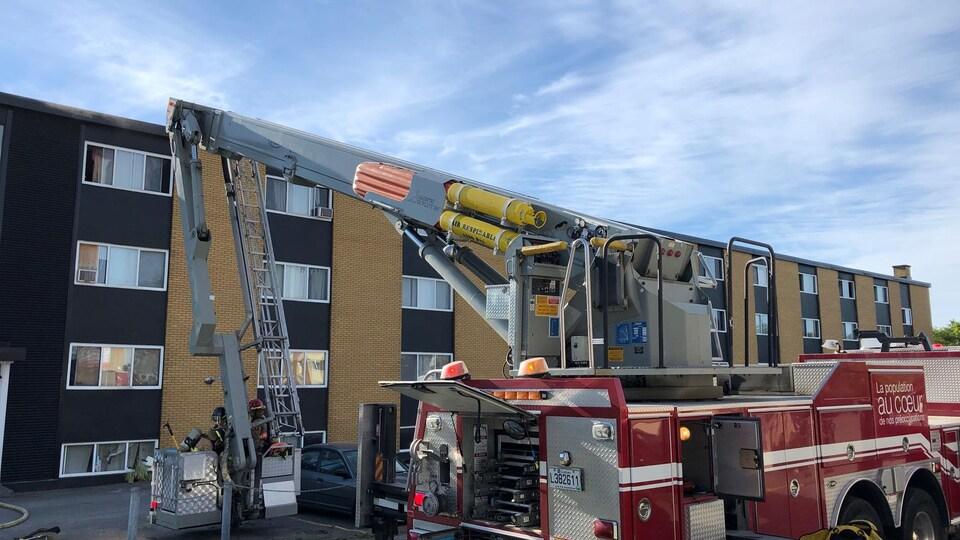 Camion de pompiers devant un immeuble.