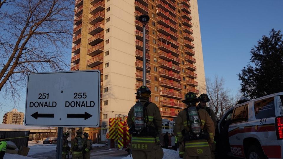 Des pompiers devant l'immeuble.