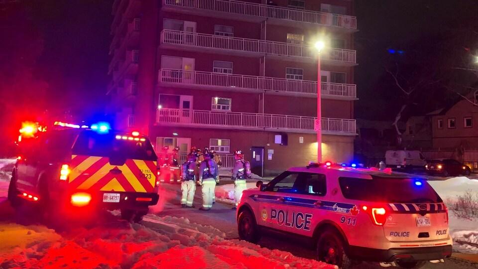 Une voiture de police devant des pompiers qui discutent près de l'édifice.