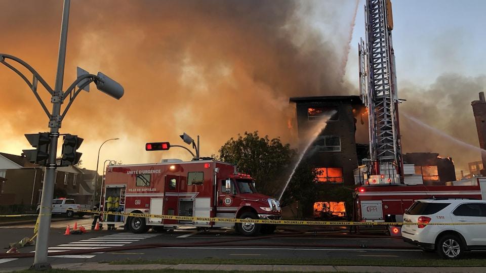 Des camions de pompier devant l'immeuble en flammes