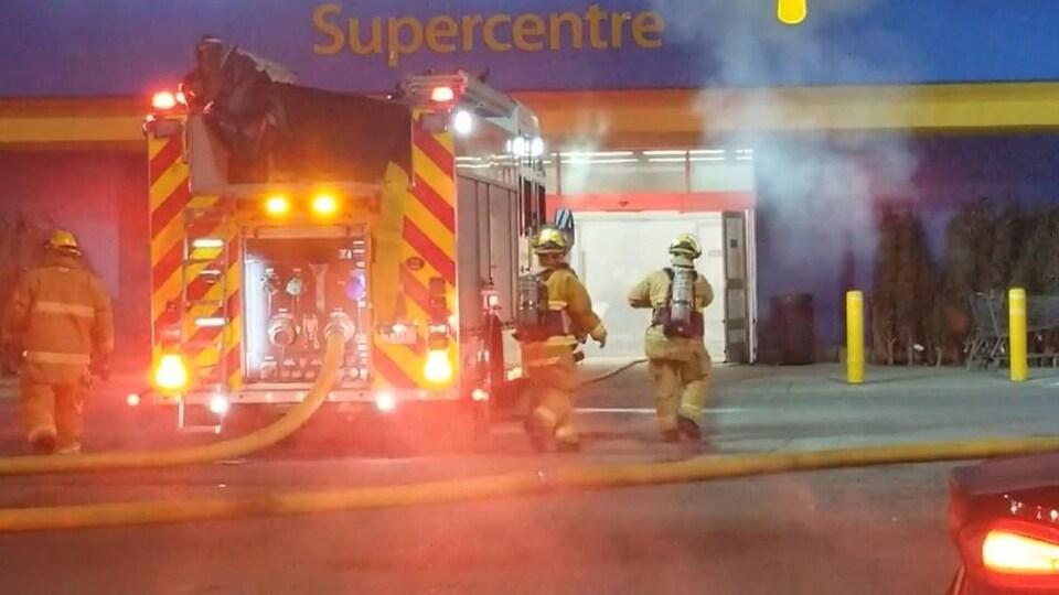 De la fumée s'échappe du magasin. Les pompiers tentent de maîtriser les flammes.
