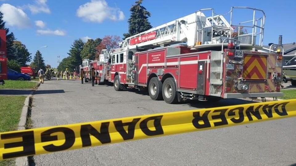 Plusieurs camions de pompiers sur le site d'un incendie.