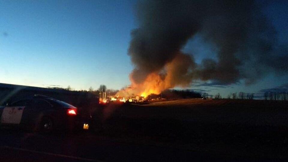 Un incendie et un immense nuage de fumée vus d'une route dans l'est ontarien.