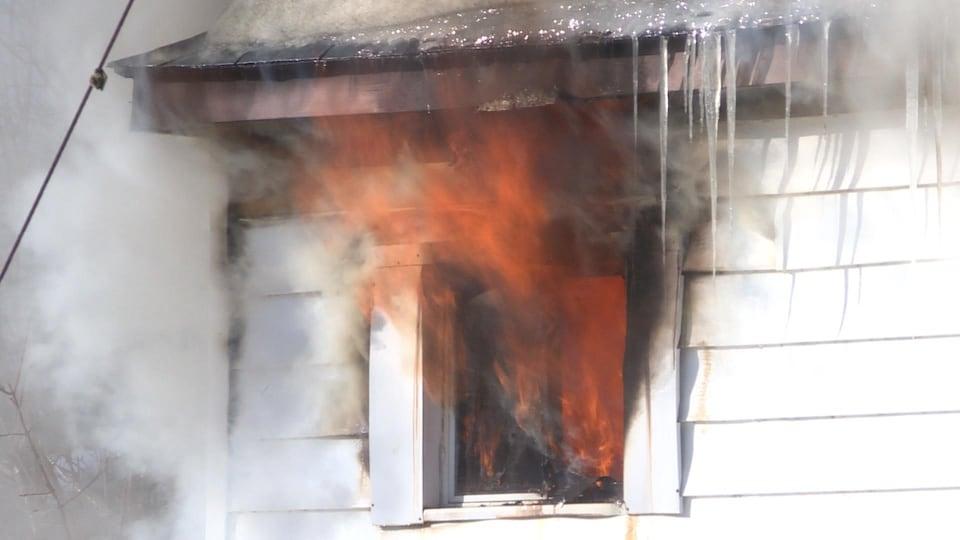 Des flammes sortent d'une fenêtre.
