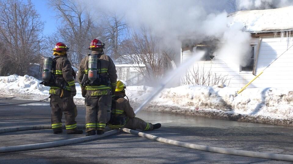 Trois pompiers et un édifice en flammes.