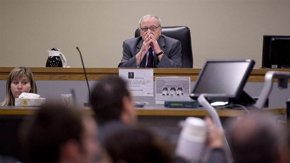 Cyrille Delâge, accoudé sur une table, face à des personnes présentes à la Commission que l'on voit de dos.