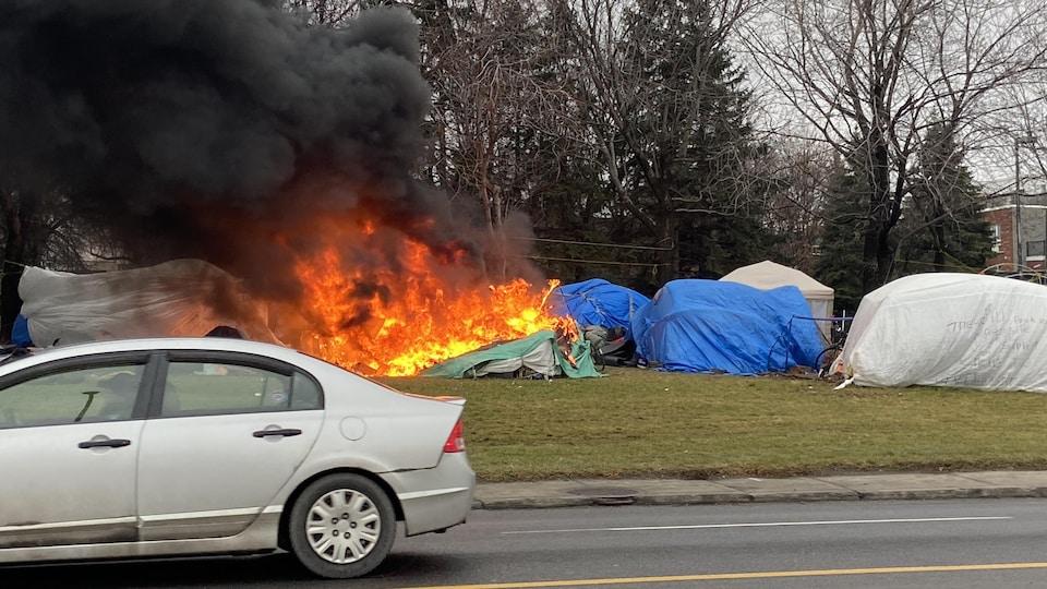 Des flammes et de la fumée noire s'échappent du campement. Une tente brûle.