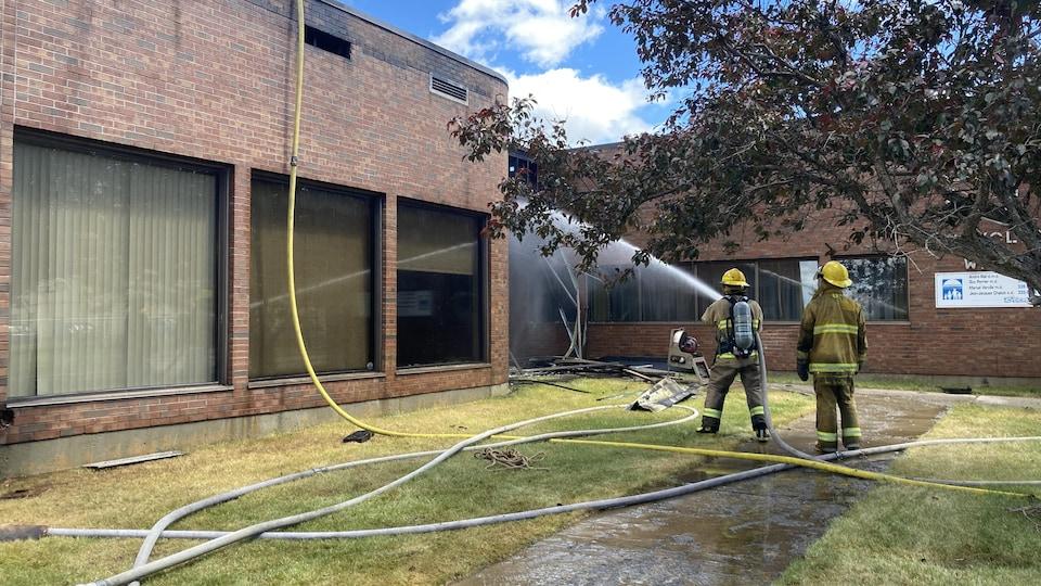 Deux pompiers éteignent l'incendie à l'aide d'un jet d'eau.