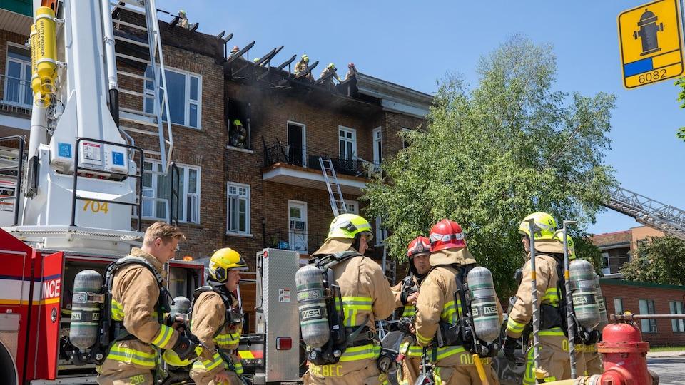 Des pompiers devant un édifice portant la marque d'un incendie