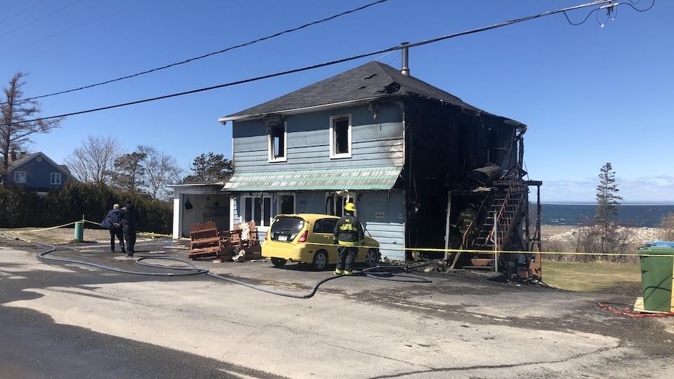 Des voisins et des pompiers constatent l'étendue des dommages.