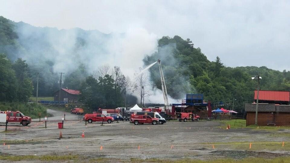 Au loin, un pompier au bout d'une échelle arrose le bâtiment principal.