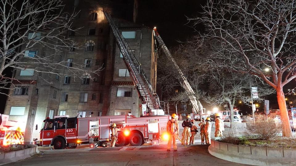 Des pompiers en intervention pour éteindre un feu dans un immeuble.