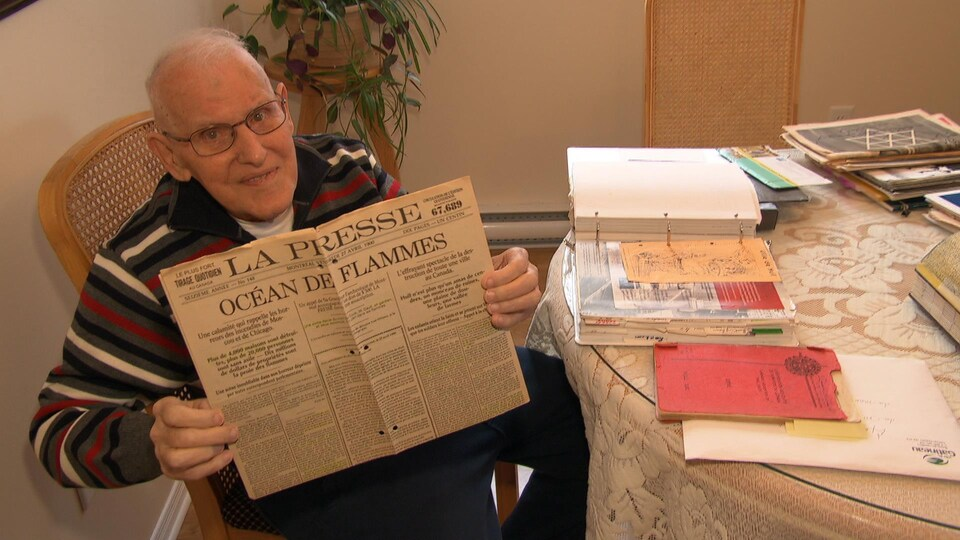 Roland Michaud qui tient la Une de La Presse qui évoque «un océan de flammes».