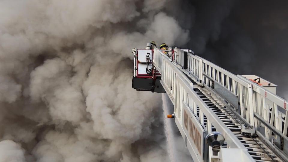 Des pompiers luttent contre un important incendie.