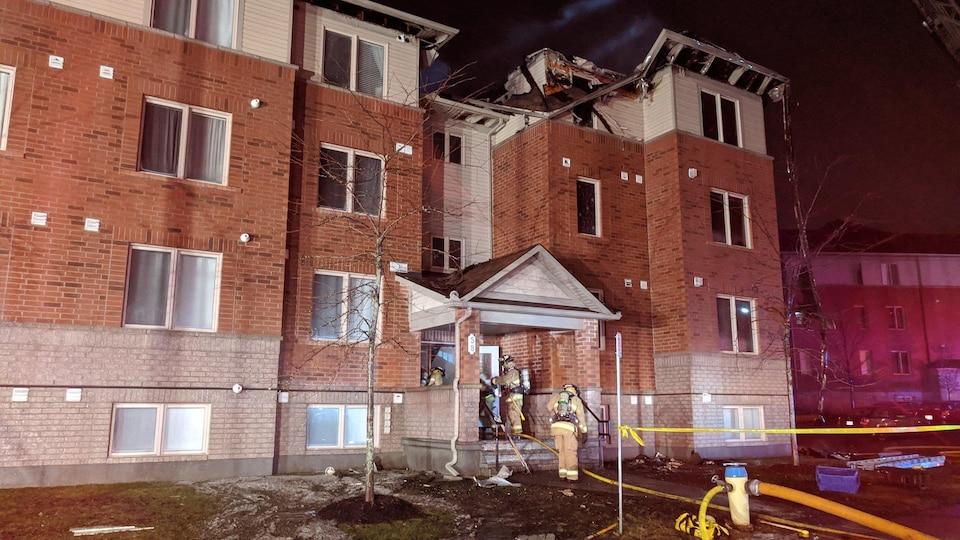 Des pompiers sont à l'entrée d'un immeuble résidentiel. Une unité de logement a été ravagée par les flammes.