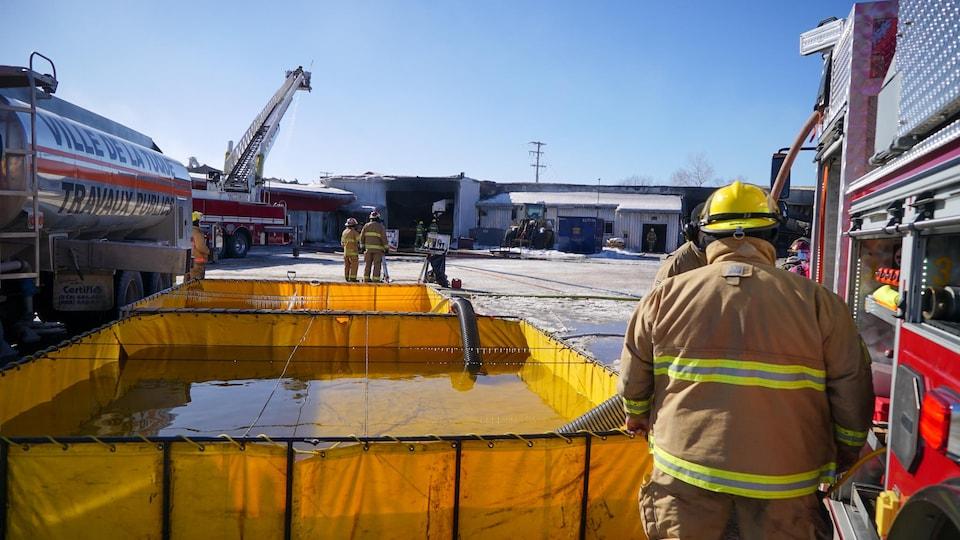 Des pompiers près d'un réservoir d'eau pour combattre un incendie en hiver.