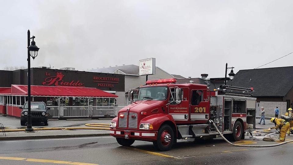 Un camion de pompiers devant un restaurant.
