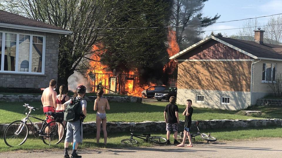 Des passants regardent l'incendie qui fait rage derrière la résidence.