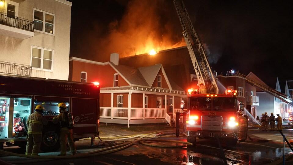 L'immeuble est en flammes. Des pompiers se trouvent devant.