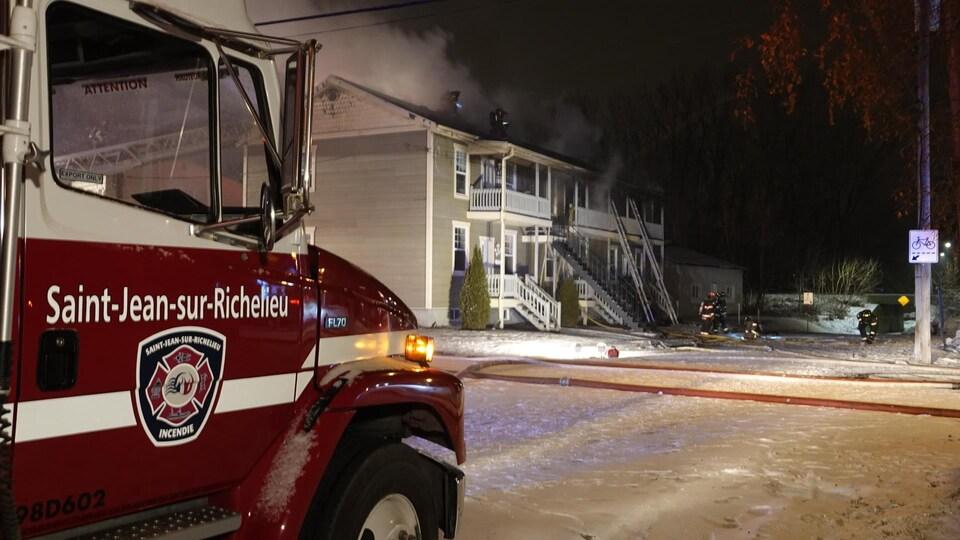 Des pompiers au pied de deux échelles posées sur la façade de l'immeuble.