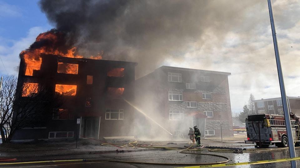 Des pompiers tentent de maîtriser les flammes.