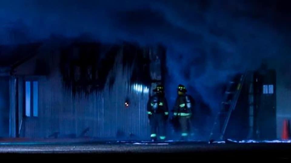 Deux pompiers devant un édifice avec de la fumée.
