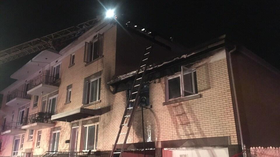 Les pompiers ont installé des échelles aériennes à la toiture pour combattre les flammes.