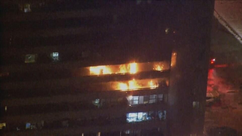 Un immeuble de logements avec des flammes sur plusieurs étages, la nuit.