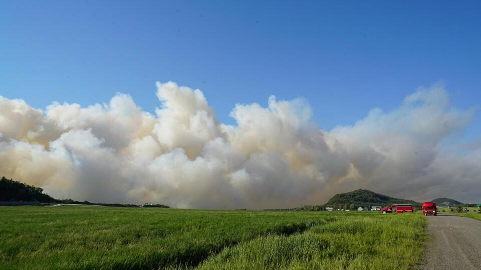Un immense panache de fumée voile le ciel. À l'avant : un champ vert.