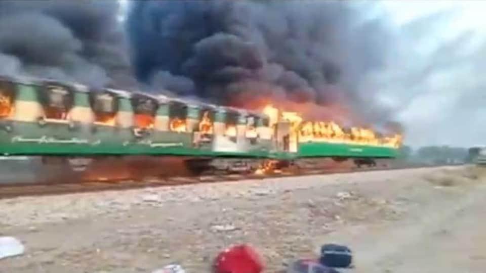 Le feu sort des fenêtres du train et crée des volutes de fumée noire.