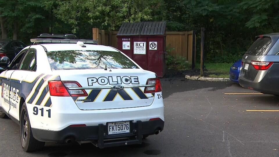 Une voiture de patrouille est stationnée devant un endroit où un début d'incendie a eu lieu.