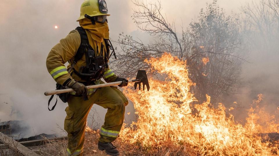 Un pompier tente d'éteindre des flammes qui ravagent la végétation.