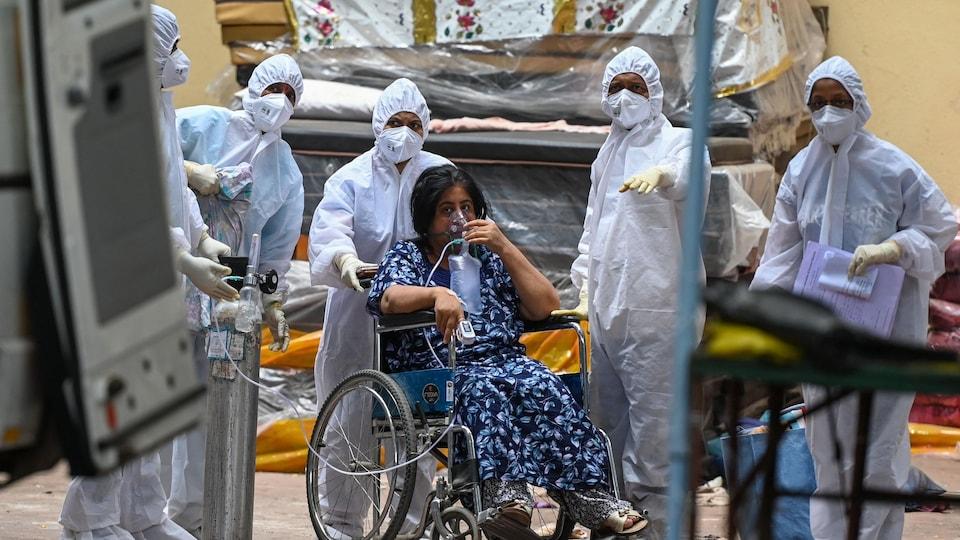 La femme est assise dans une chaise roulante et utilise un masque à oxygène. Elle est entourée de plusieurs personnes portant des habits de protection.