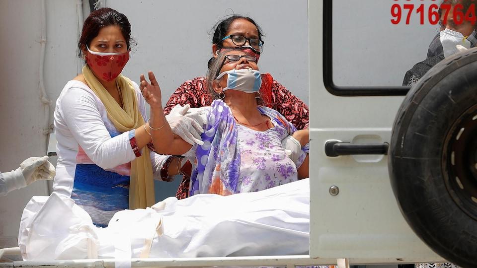 La femme pleure, soutenue par deux autres femmes devant le corps, enveloppé d'un drap blanc.