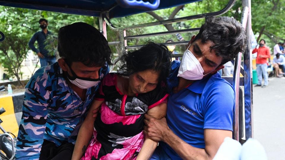 Une femme très affaiblie soutenue par deux hommes en Inde.