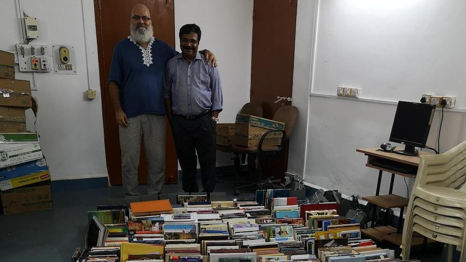 Carlos Bergeron et un professeur devant les milliers de livres.