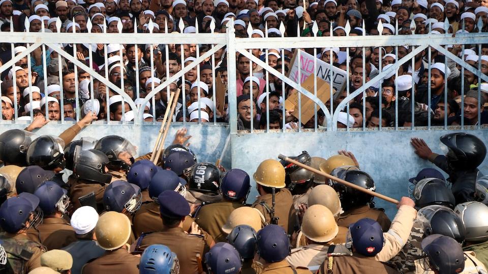 Des policiers casqués et armés de bâtons sont retranchés derrière une grille, se protégeant de plusieurs centaines de manifestants musulmans.