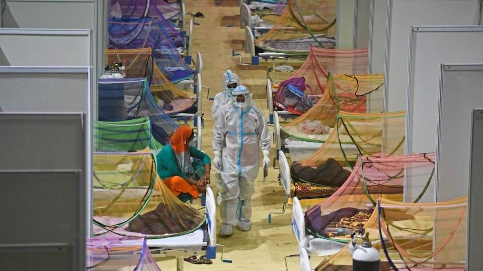 Des travailleurs de la santé vêtus de masque et de tuniques se promènent dans la rangée entre une série de lits isolés par des séparateurs. Chaque lit possède un filet moustiquaire.